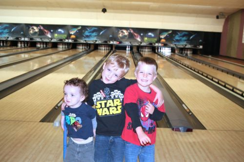 3 young boys standing in front of the lanes