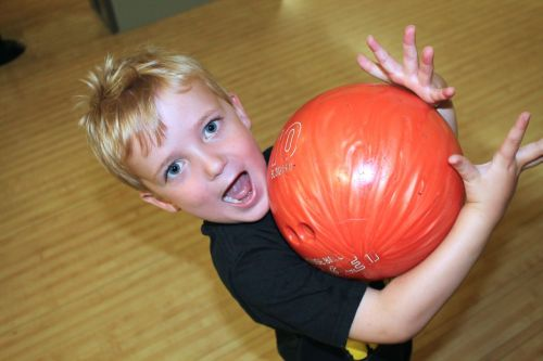 Young boy holding a bowling ball